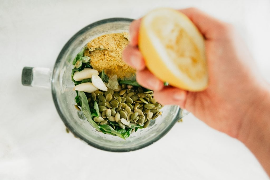 A hand squeezes juice from a lemon into a blender which contains other ingredients for a vegan pesto recipe.