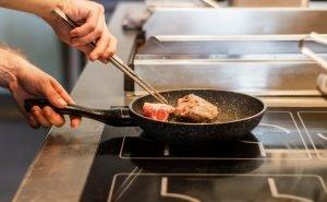 Searing steak in stone cookware.